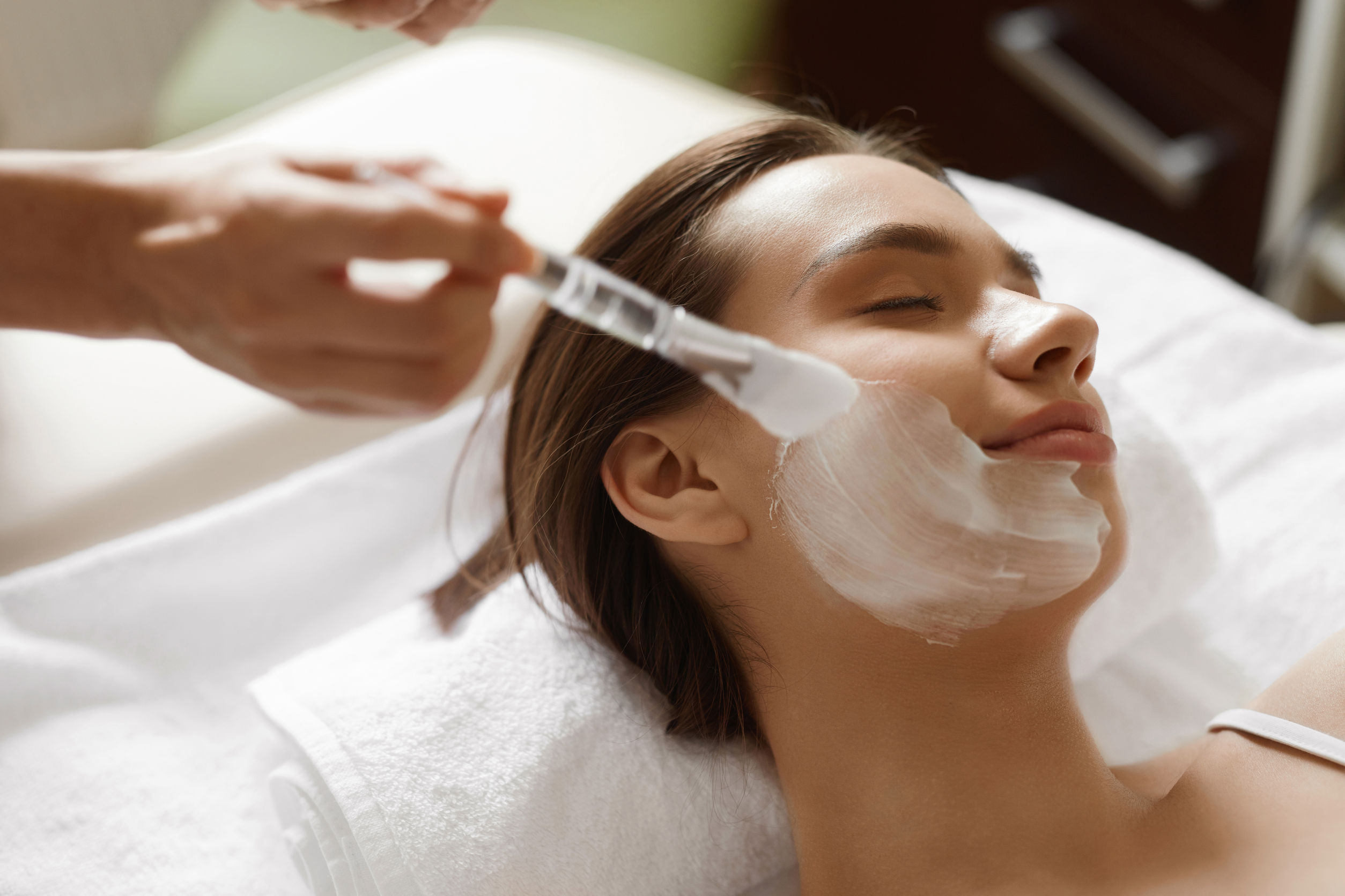 61052501 - skin care. beautiful healthy woman getting cosmetic mask at spa salon. closeup of cosmetologist hands applying mask with brush on females face. facial beauty treatment concept. high resolution image